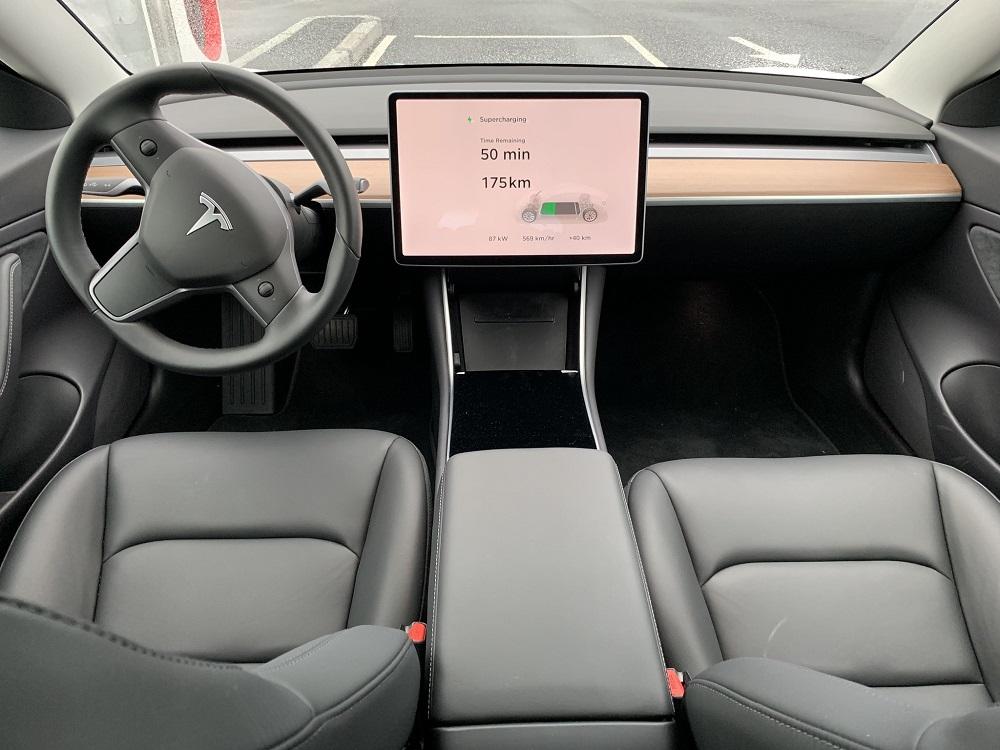 På innsiden av en Tesla som lader